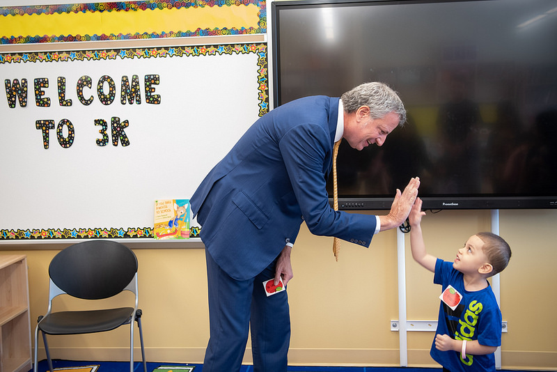 Mayor de Blasio high-fiving little boy