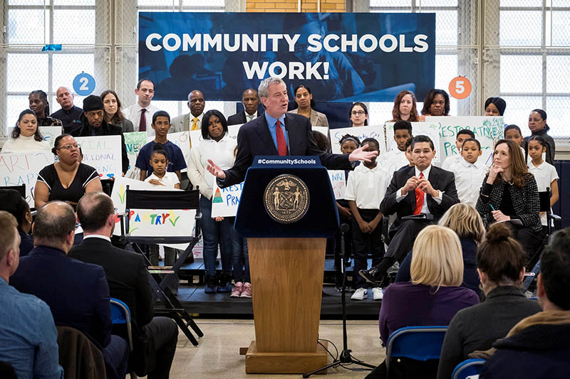 Mayor Bill de Blasio stands at a podium in front of students and teachers