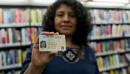 Woman holding an IDNYC card in a library