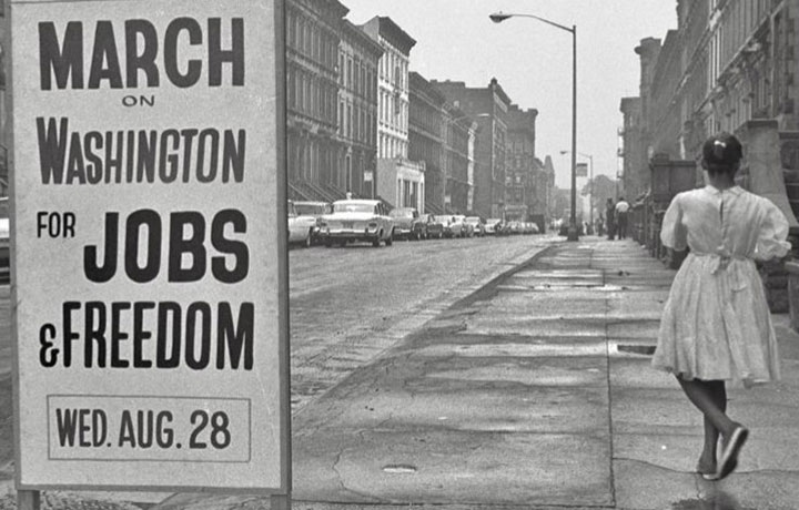 Black and white photo of girl standing next to sign that says March on Washington for Jobs & Freedom