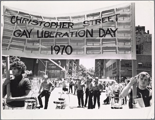 A black and white photo of people marching holding up a banner that states Christopher Street Gay Liberation Day 1970