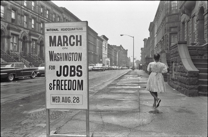 a vintage black and white photo of a view  down a block of house and a sign on the side walk posted National Headquarters March on Washington for Jobs and Freedom Wed August 28