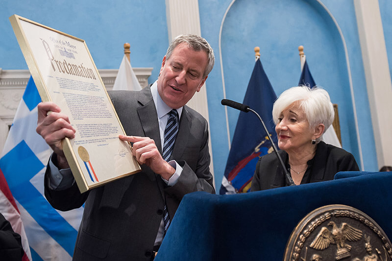 Mayor de Blasio points to the text of the Proclamation while Olympia Dukakis looks on.