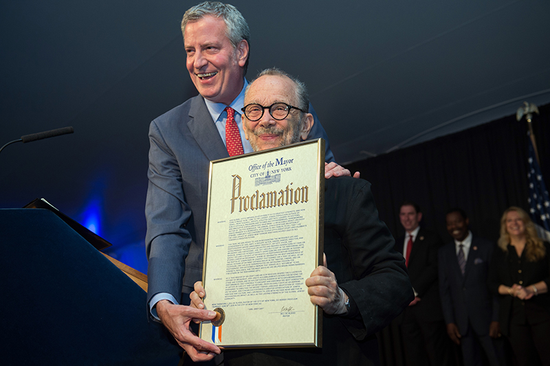 Mayor Bill de Blasio on stage with Joel Grey who is holding his proclamation