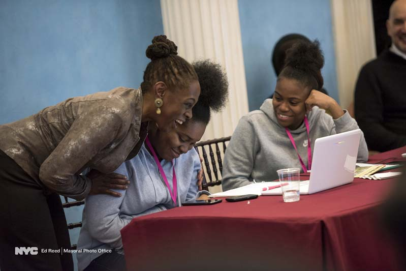 First Lady Chirlane McCray smiling with two girls at coding workshop