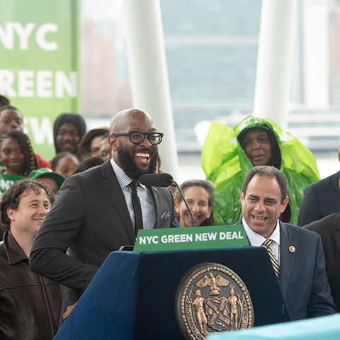 Representatives at a podium discussing the NYC Green New Deal