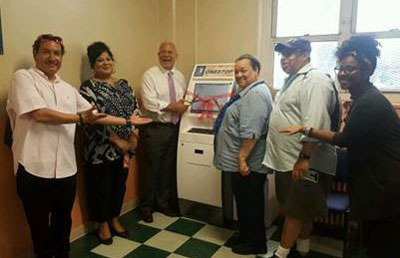 NYCHA General Manager (Third Left) and Tenant Association President Carol Wilkins (Third Right) unveil NYCHA's new kiosks with Property Manager Anita Lal (Second Left) and staff from Congresswoman Maloney, Assembly Member Nolan and State Senator Gianaris's offices.