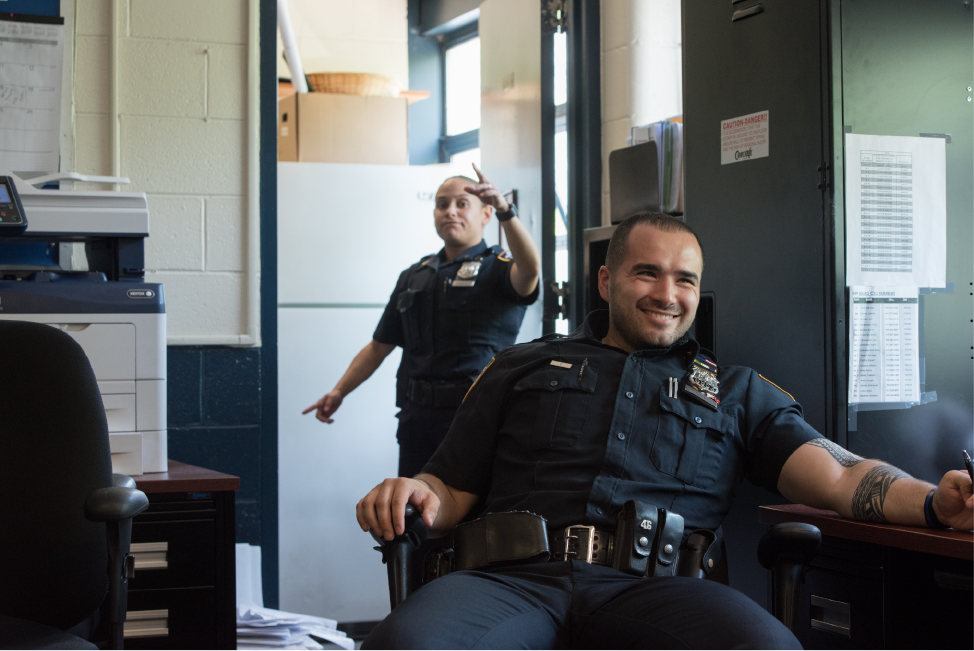 Sanchez and Mujaj at desks in the precinct
