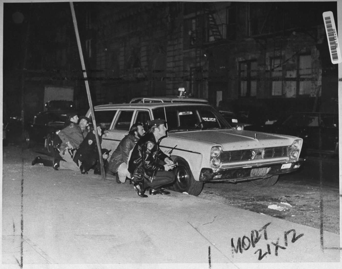 Police officers behind a car near the crime scene