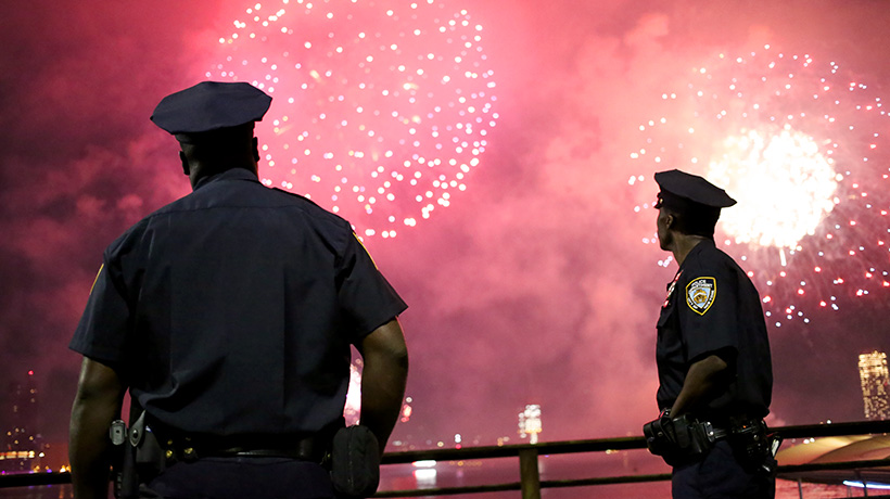 Two police officers silhouetted against a sky of fireworks