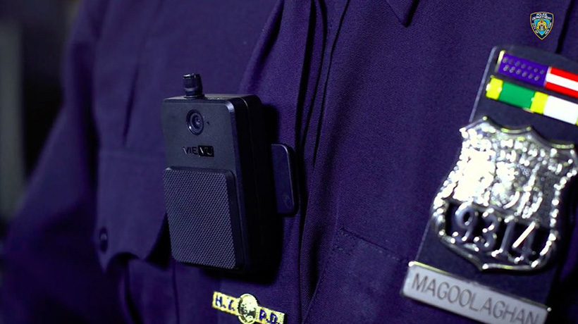 Close up of a body-worn camera clipped to the uniform shirt of a police officer