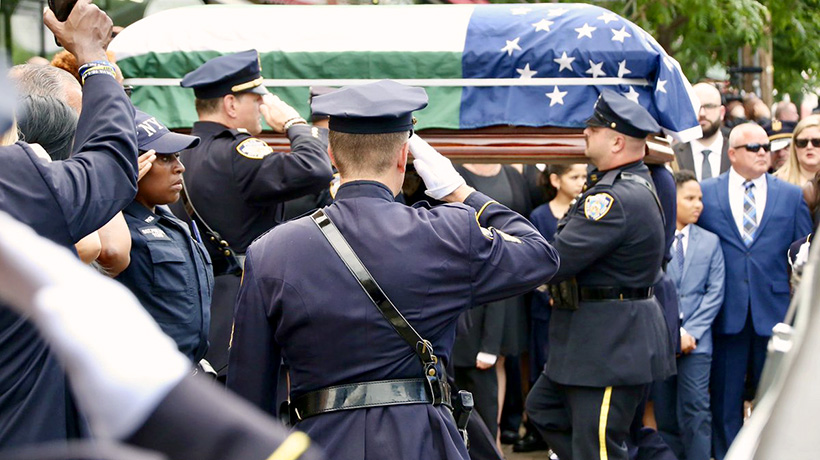 Officers in dress uniform saluting a NYPD-flag-draped coffin