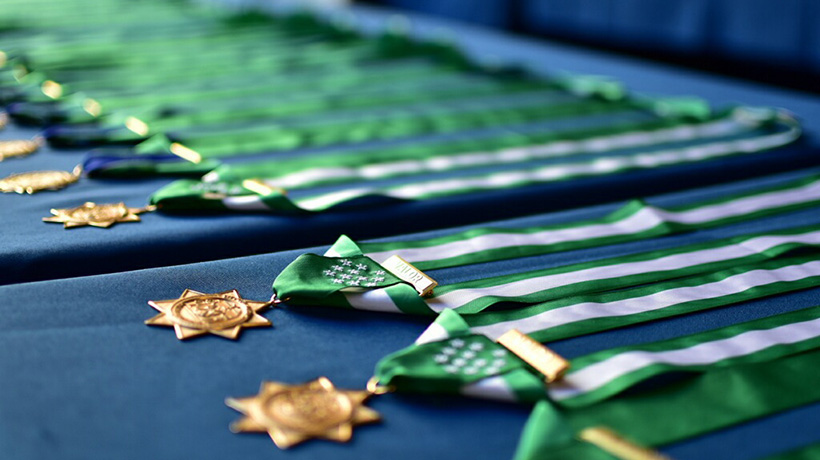 Medals of Valor, with their green bands, lined up on a table with a blue table cloth