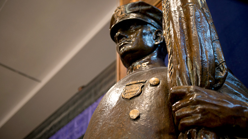 Statue of a police officer in front of memorial wall in lobby of One Police Plaza