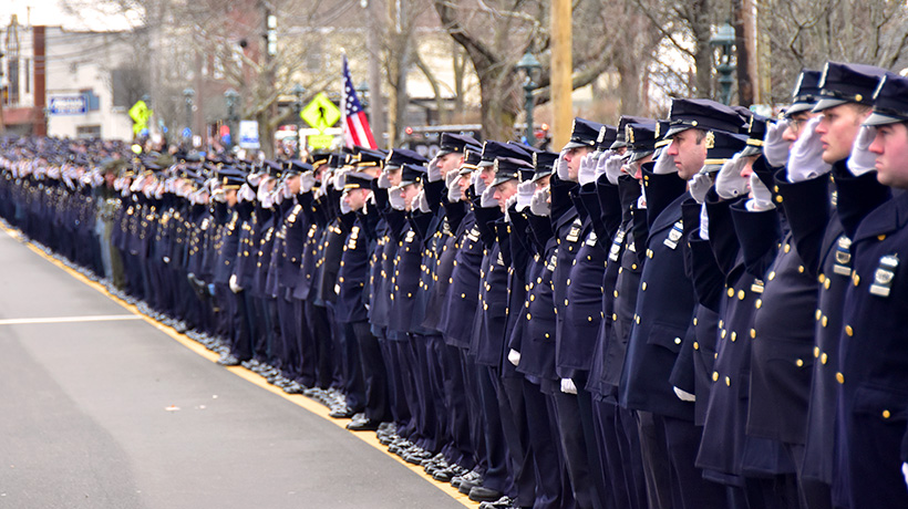 Long line of police officers saluting in dress uniform