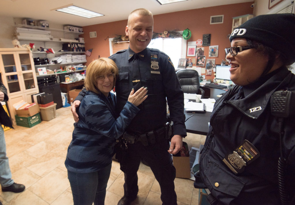 Woman hugging one police officer, another police officer standing near and smiling