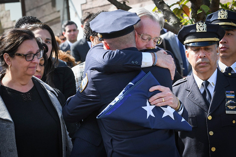 Fallen officer Brian Mulkeen's father acceping a folded American flag and hugging another officer