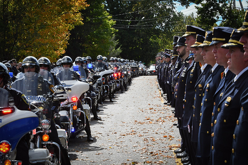 Street upstate lined with police officers in uniform and officers on motorcycles, going back as far as can be seen