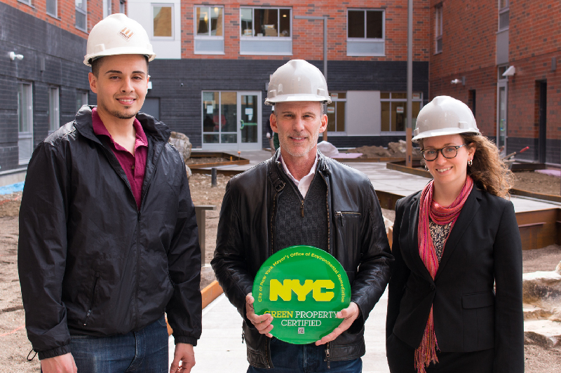 "Group in construction hats holding a sign that reads, ""NYC Green Project Certified"""