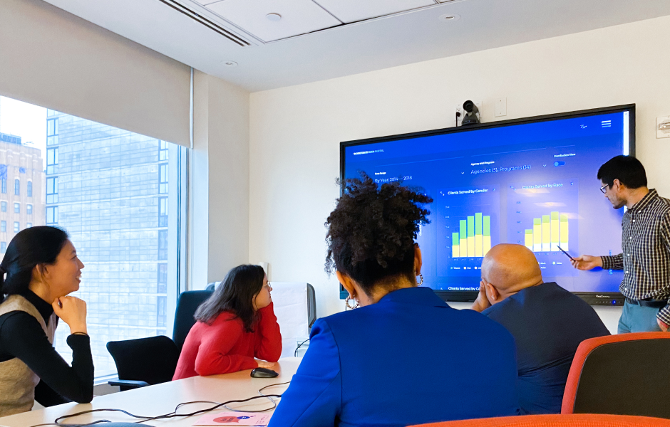 Group of coworkers in a conference room reviewing workforce data and graphs on a large screen