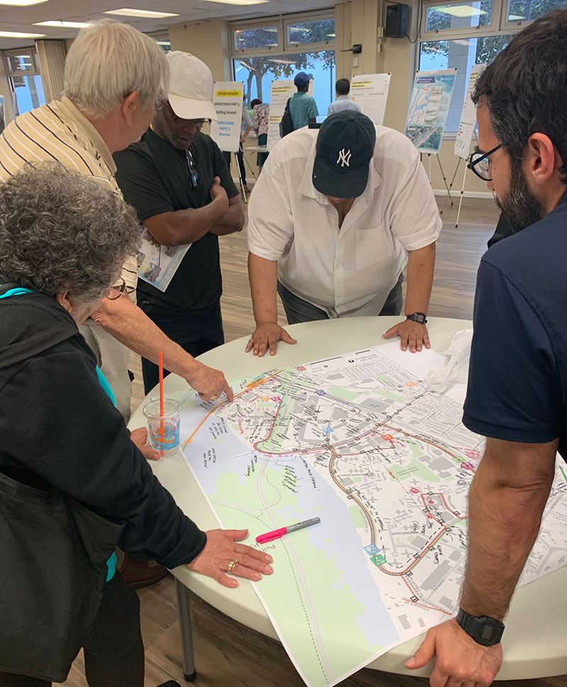 Planning staff speak with Co-Op City residents using a map to mark up likely routes to and from the Metro-North station area.