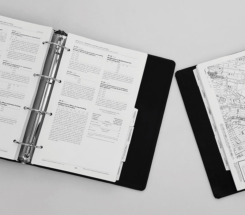 Open binders with text and maps