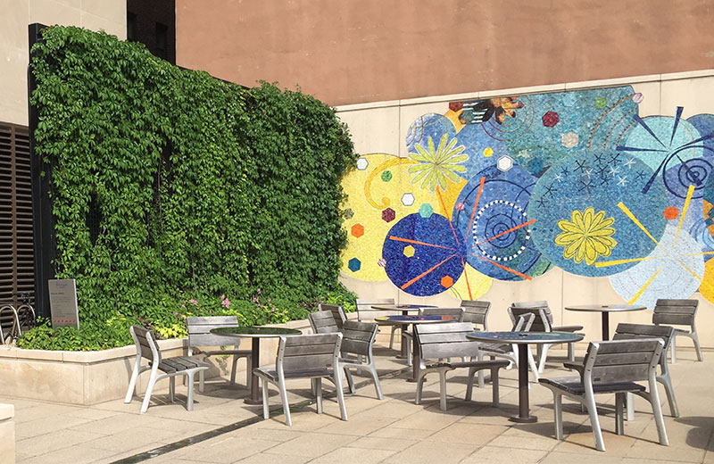 Screening blank walls with planting and artwork improves attractiveness of the plaza