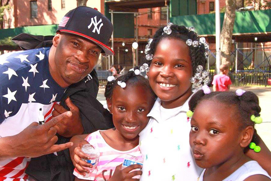 man with Yankees hat and three girls holding water bottles and smiling in front of building
