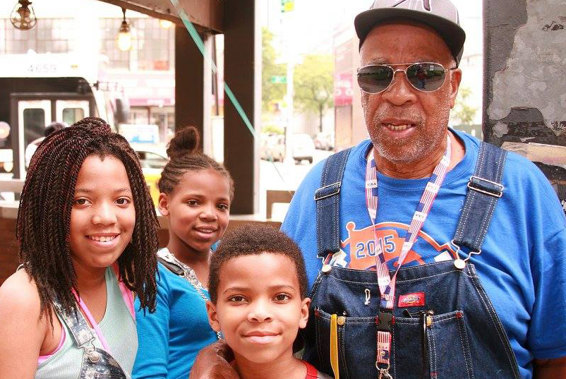 older man with sunglasses posing with two girls and one boy for a photo