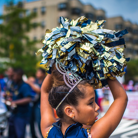 girl with cheerleading pom poms at parade