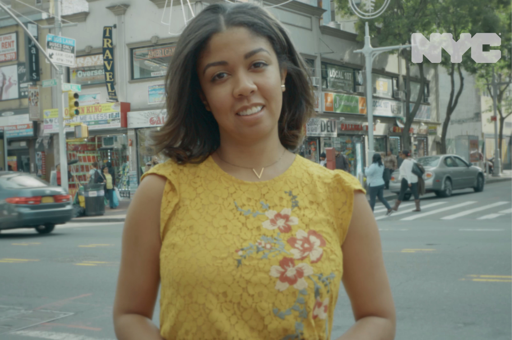 Screenshot from a video of a young woman standing at a NYC intersection.