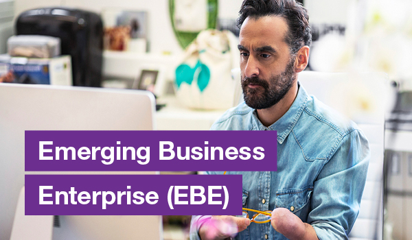 Man with limb difference using computer with text on the left that says Emerging Business Enterprise (EBE)