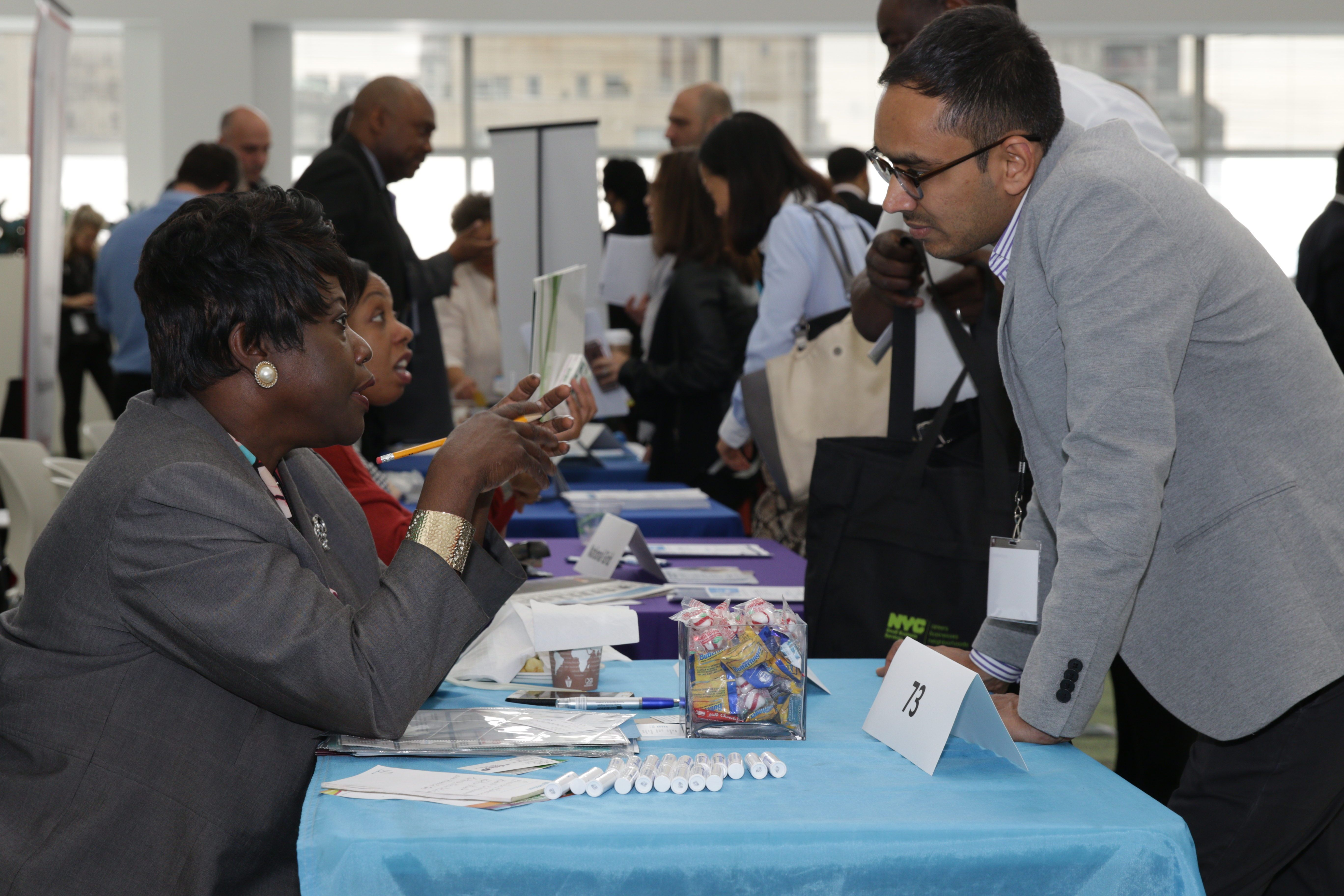 A City representative is assisting a business owner at the annual Citywide Procurement Fair