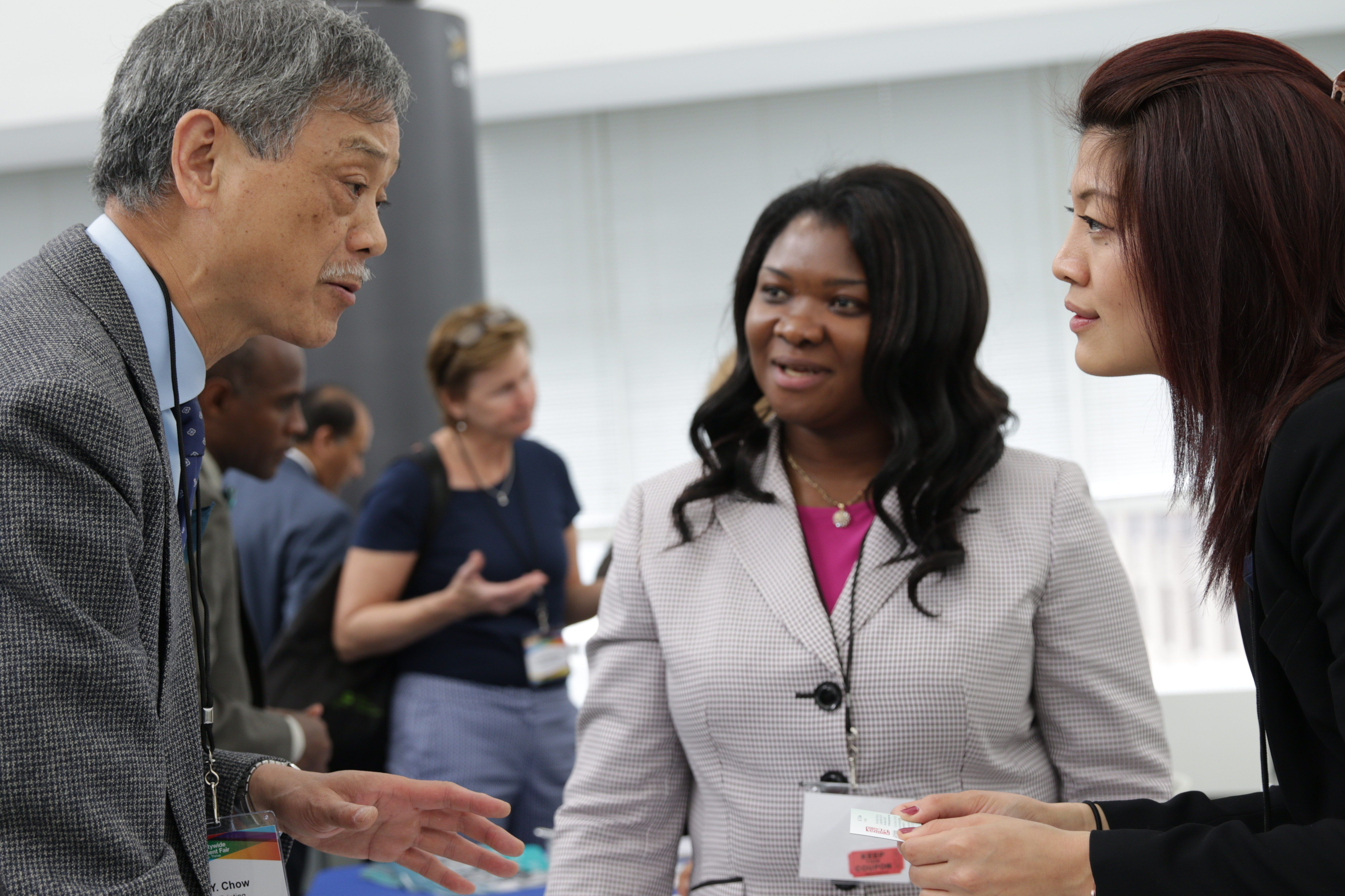 An Asian man, Asian woman, and black woman are in a discussion at the S.B.S. M.W.B.E Procurement Fair.