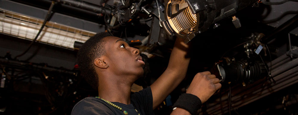 Young man adjusting lights in a theater