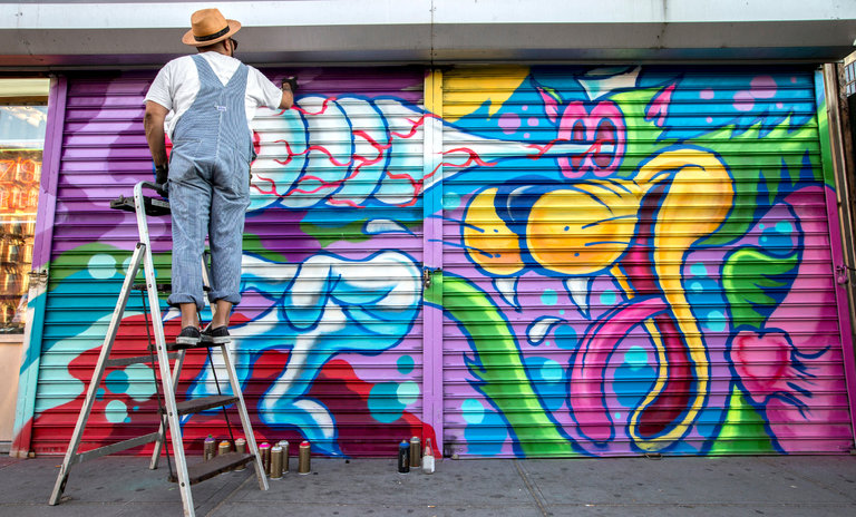 artist on ladder painting mural on pull-down security gate on Lower East Side
