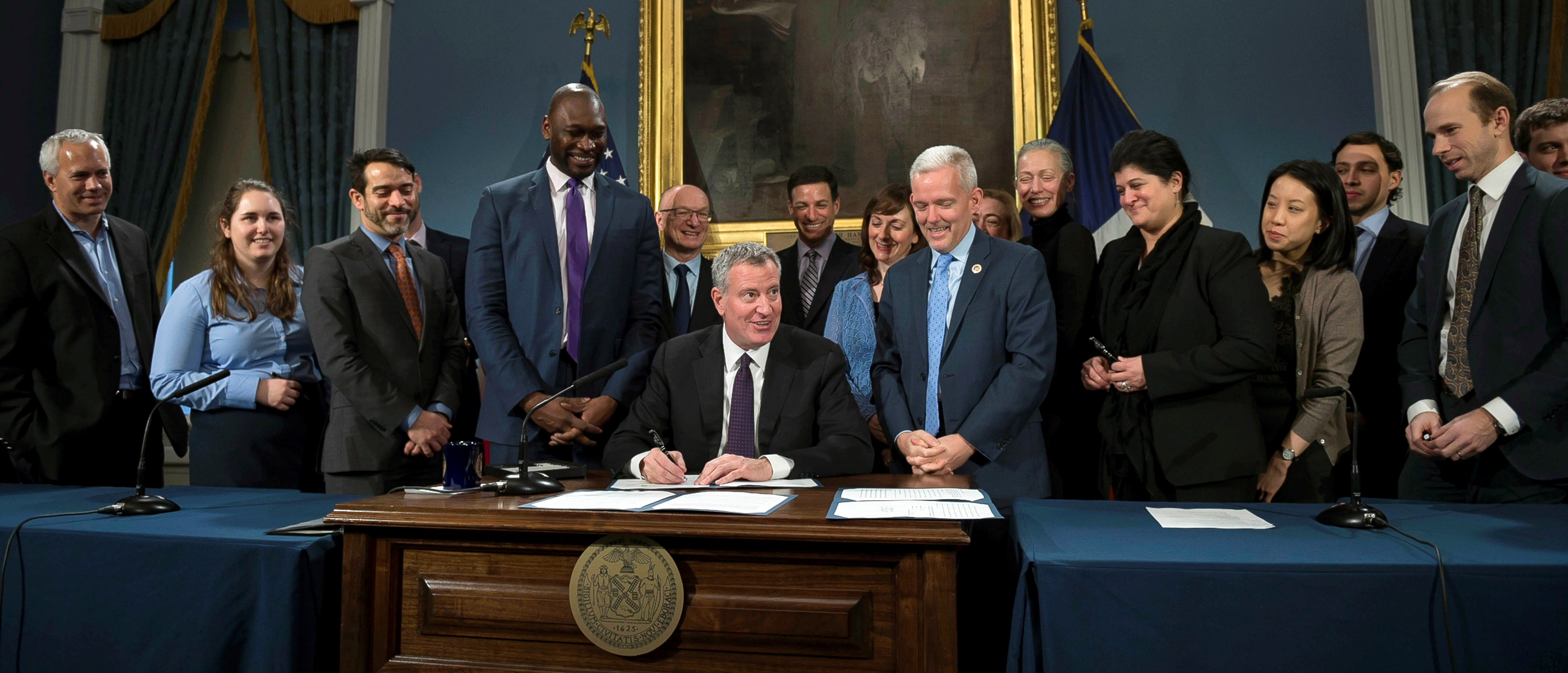 mayor bill de blasio signing bill at desk, surrounded by stakeholders