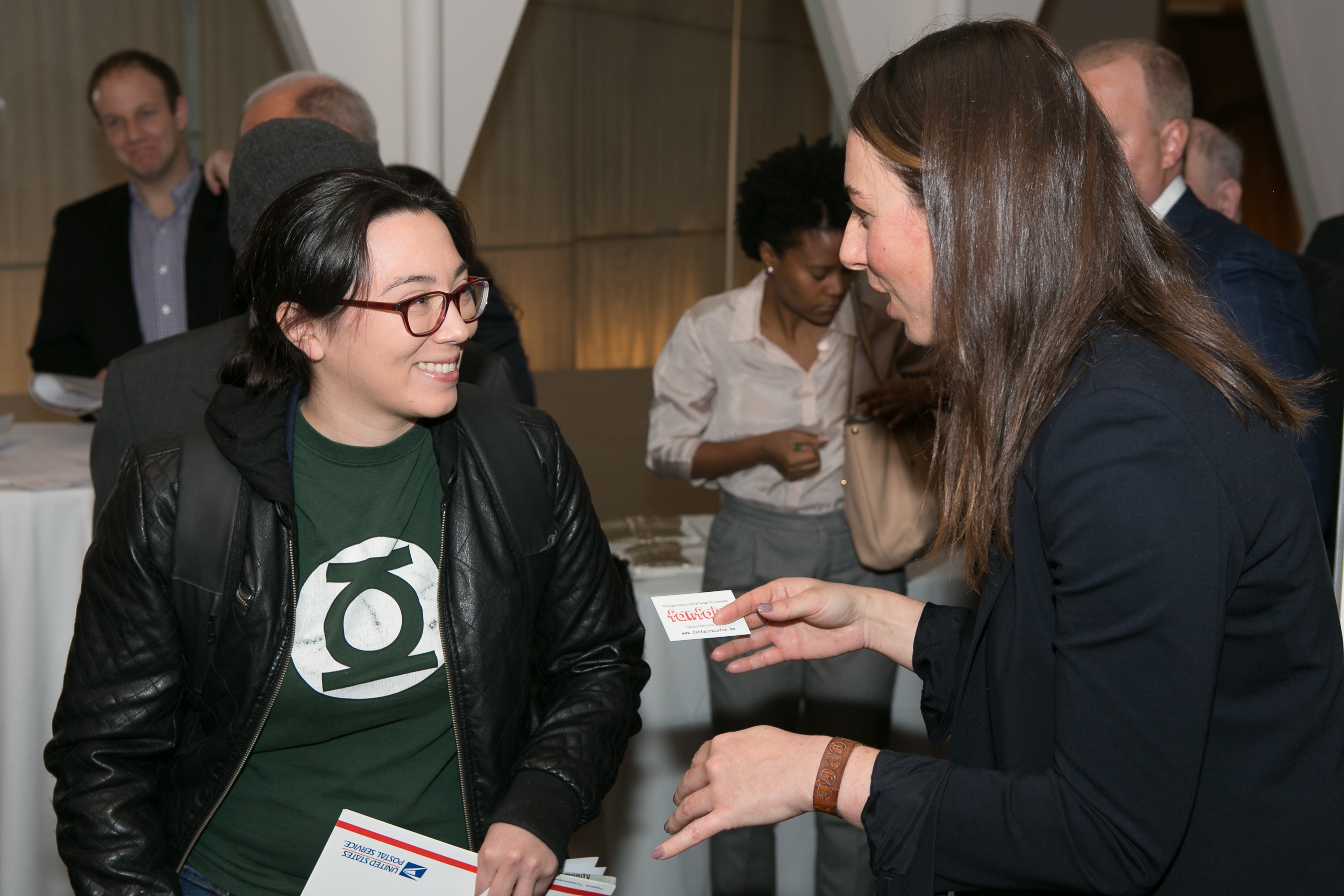 Two people talking at a networking event and exchanging business cards