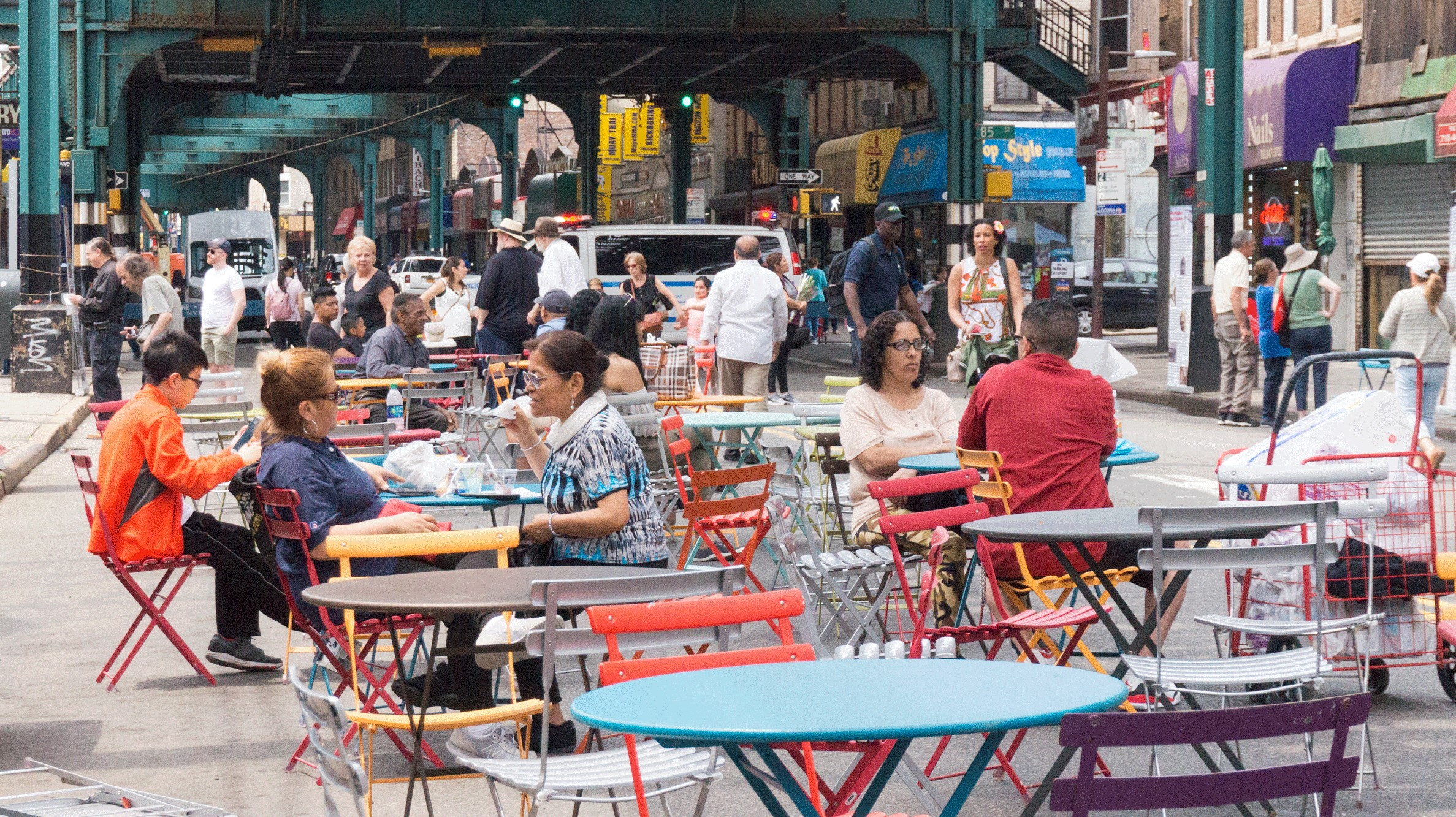 street scene with people seated at community tables under an elevated train track
