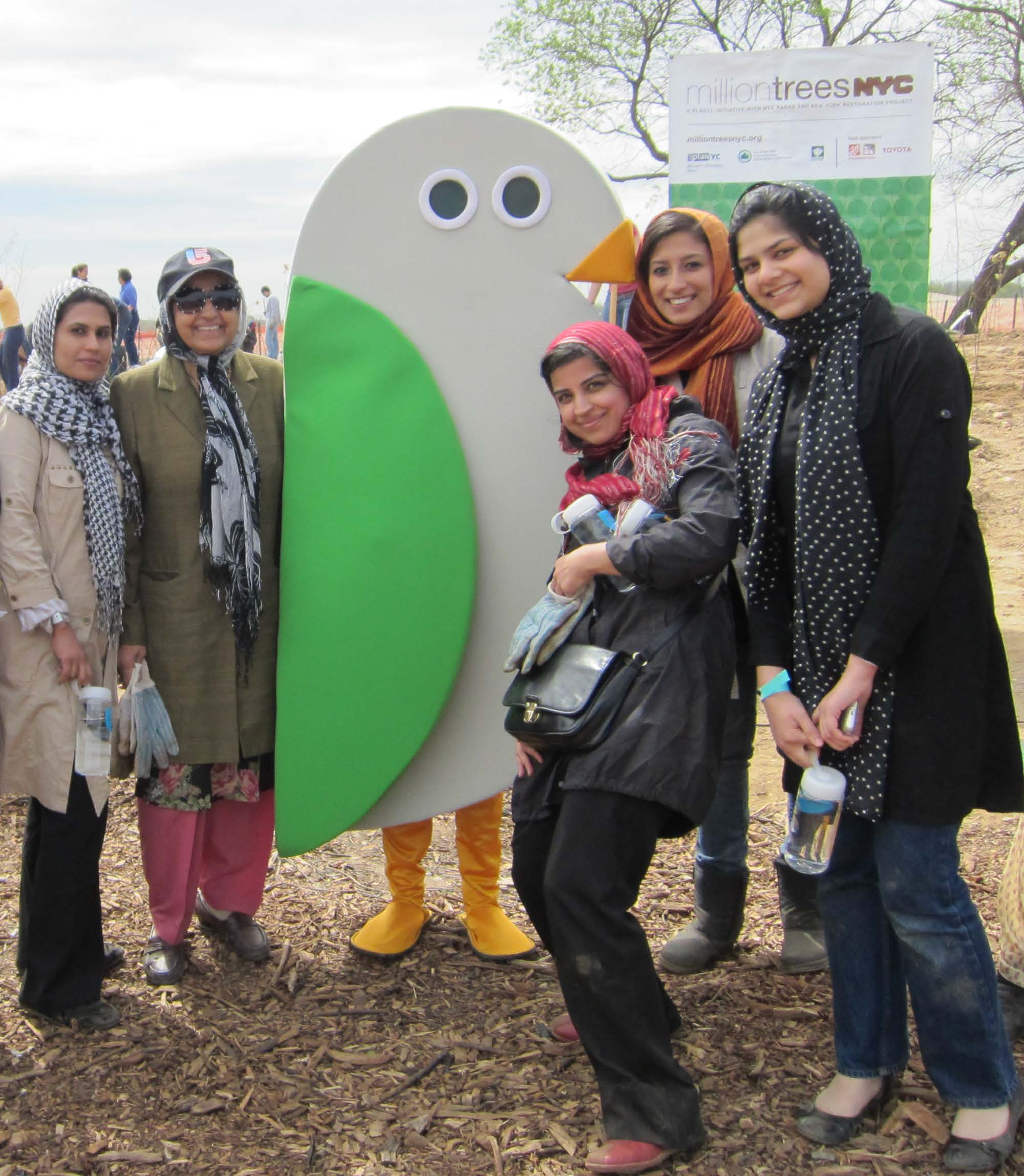 People posing with the GreeNYC mascot, Birdie