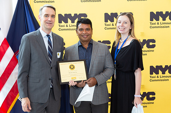 Acting Commissioner Bill Heinzen honors a Safe Base Honoree and ceremony speaker Bijoy Saha of Mavrik Transportation.
