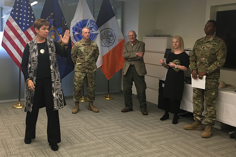 Commissioner Sutton gestures with an Army knife hand as she speaks at Deputy Commissioner Roth's promotion ceremony