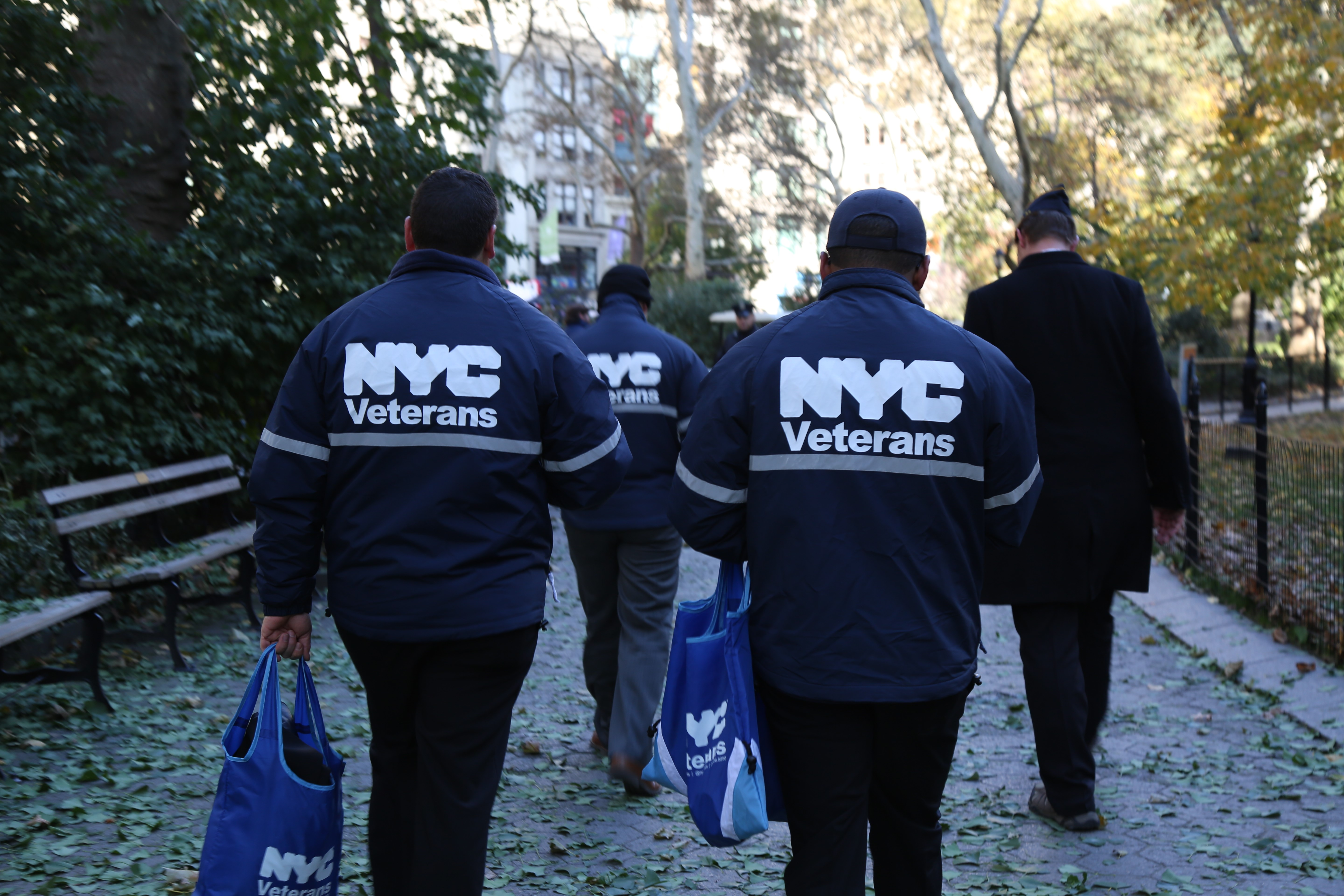DVS staff walking during Veterans Day activities, their backs facing the camera showing NYC Veterans logo on their jackets.