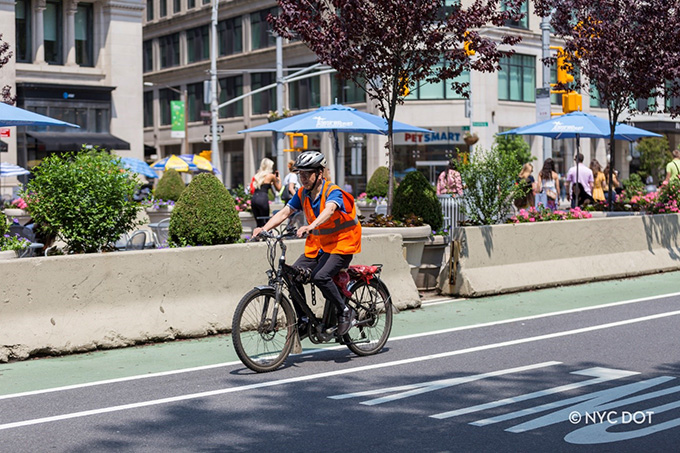 A delivery person riding an e-bike wears a helmet and orange safety vest while riding on a green bike lane.