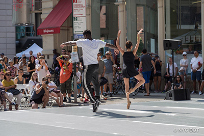 Dancers perform outside on a stage during Summer Streets