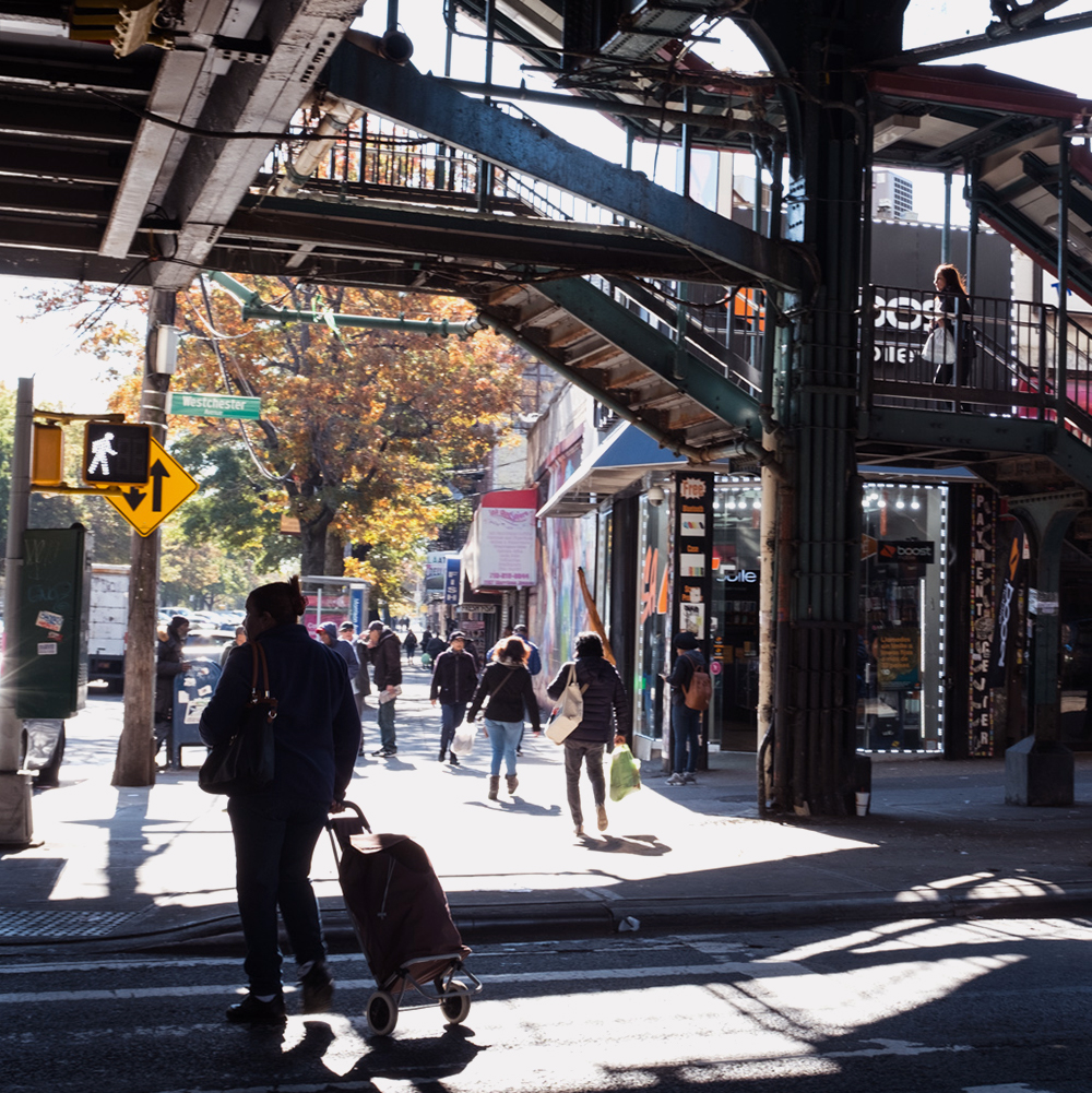 A person crossing a street under an elevated train line